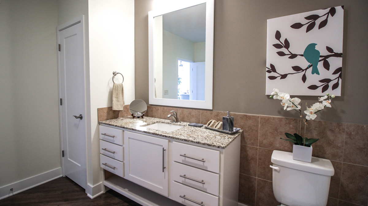 Apartment bathroom vanity with granite counters and white mirror.