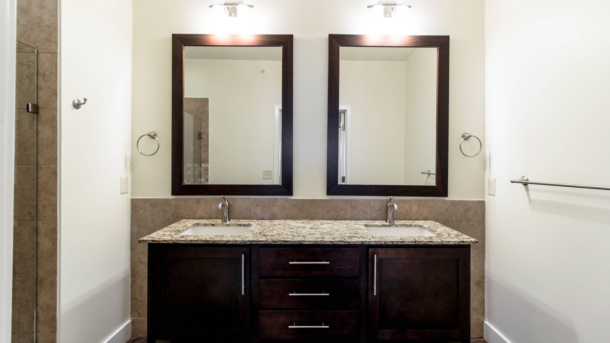 Bathroom view with double sink vanities.